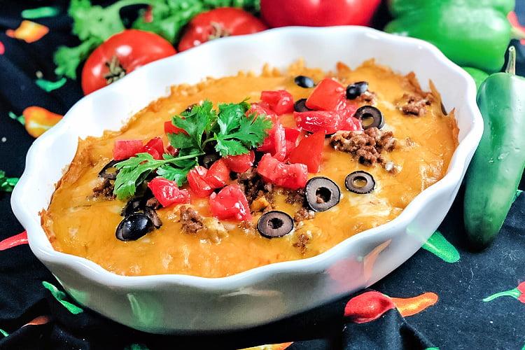 A white casserole dish loaded with enchilada casserole.