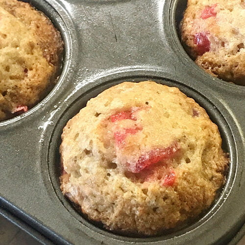Baked banana cherry muffins in a muffin tin.
