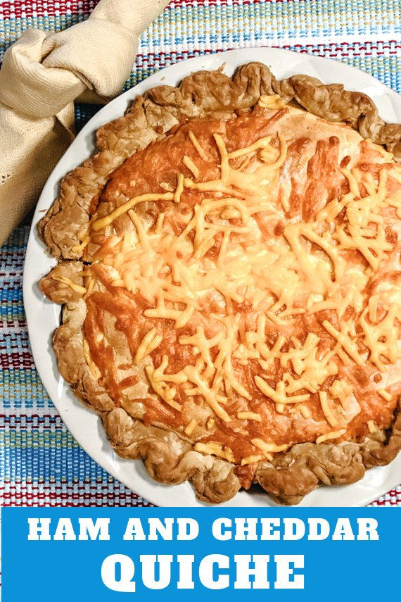 A Ham and Cheddar Quiche in a white deep-dish pie plate.