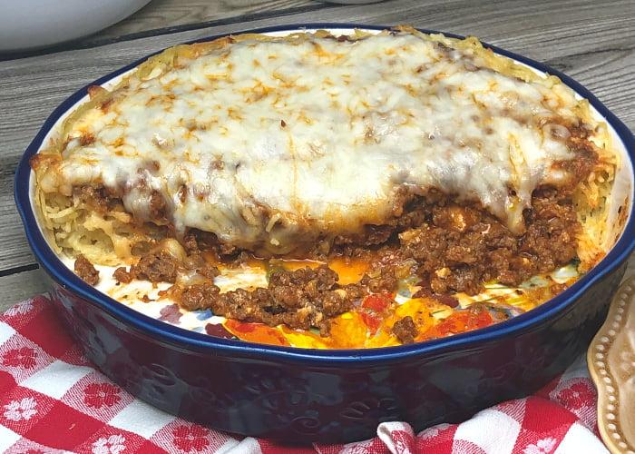 Half a spaghetti pie in a round casserole dish.