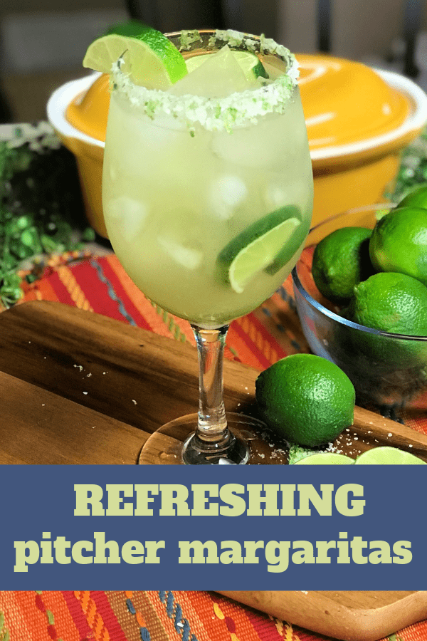 A refreshing margarita served in a stemmed glass with sliced limes and salt.