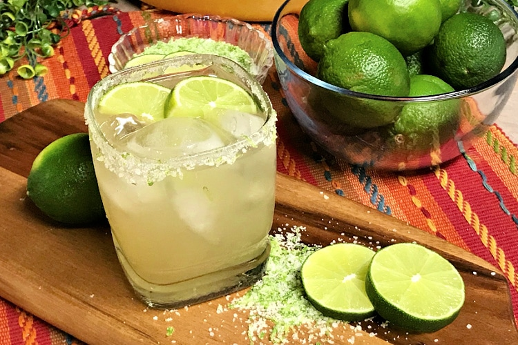 A margarita served in a cocktail glass garnished with slices of lime.