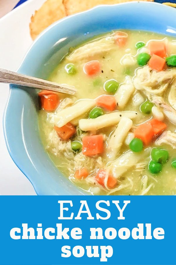 A light blue bowl holding chicken and noodle soup with veggies.