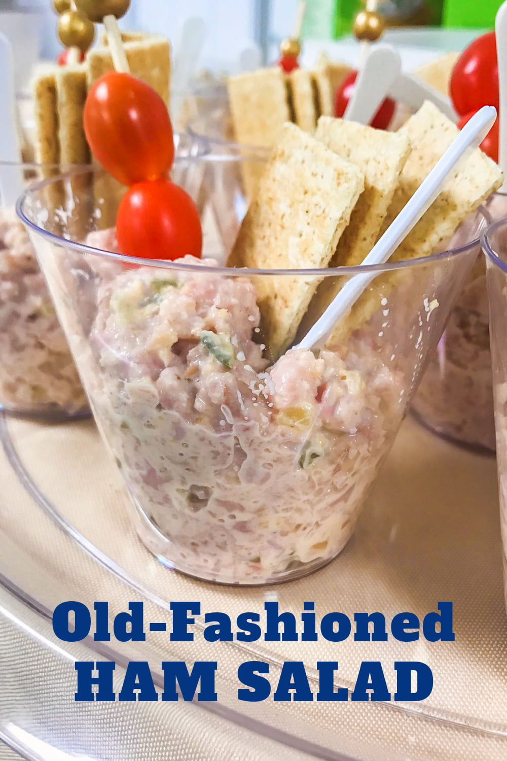 A cup of ham salad with grape tomatoes and crackers.
