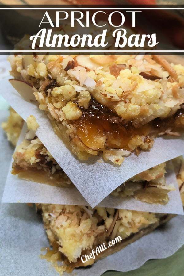 Three squares of apricot almond bars, stacked on top of each other with parchment squares in between each one.