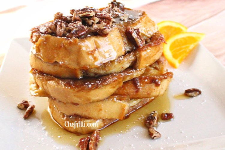 Sliced of French toast stacked upon each other with pecans an syrup.