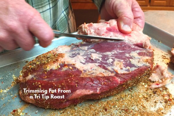 Use a sharp knife to trim the fat from a tri tip roast.