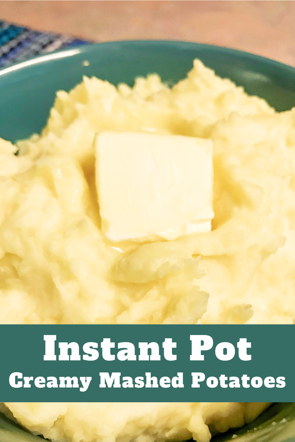A bowl loaded with creamy mashed potatoes with a melting pat of butter on top.