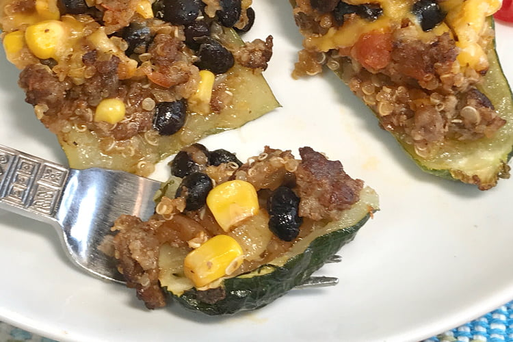 A big forkful of zucchini burrito boats with Mexican sausage filling.