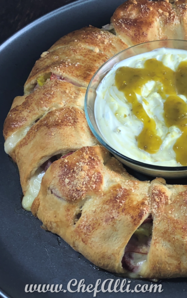 This Spicy Italian Sub Crescent Ring is a great way to serve a crowd. It's loaded with all of your favorite Italian sub flavors, then baked in buttery, flaky crescent roll dough. I like to serve it with a good dollop of mayonnaise and Sarah Jane's Jalapeno Mustard. Yum! #crescentring #ItalianSubRecipe #SarahJanes