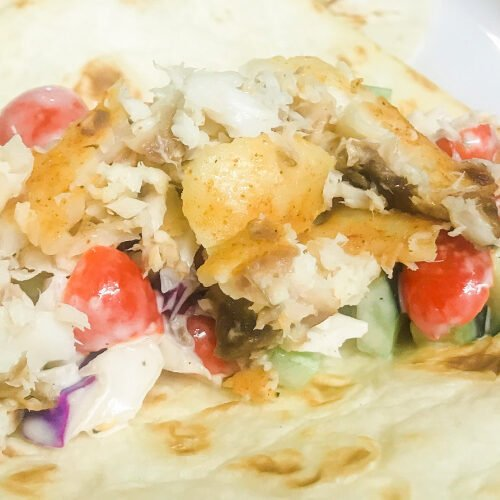 Crumbled tilapia fillets with cucumber salsa on top of a flour tortilla.