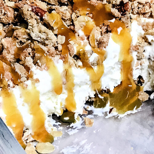A pan of butter brickle ice cream dessert with caramel dripping down the edge.