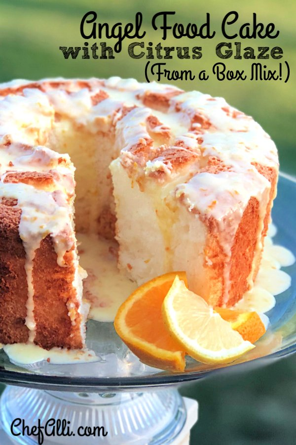 Angel Food Cake with Citrus Glaze sitting on a cake stand with one slice removed.