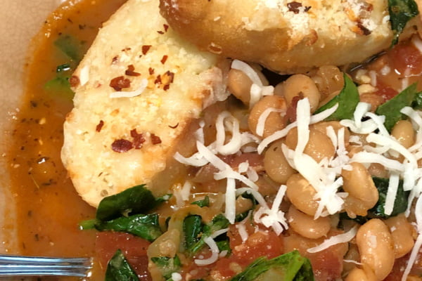 A close up shot of Tuscan Bean Soup in a bowl, topped with parmesan cheese and crostini.