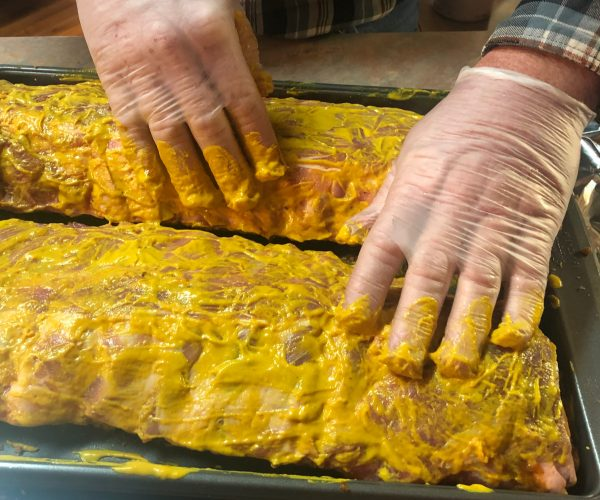 Two racks of ribs being rubbed with mustard.