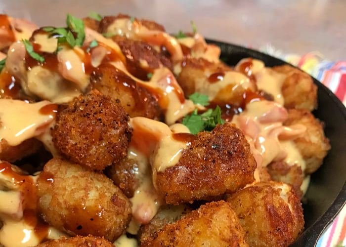 Twisted Mexican Hot Tots layered into a skillet with queso.