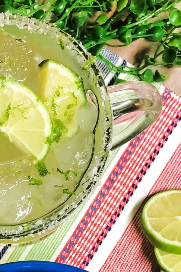 Overhead shot of a margarita in a glass with limes.