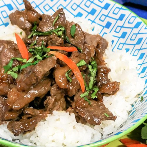 A bowl with rice topped with beef bulgogi and cilantro.