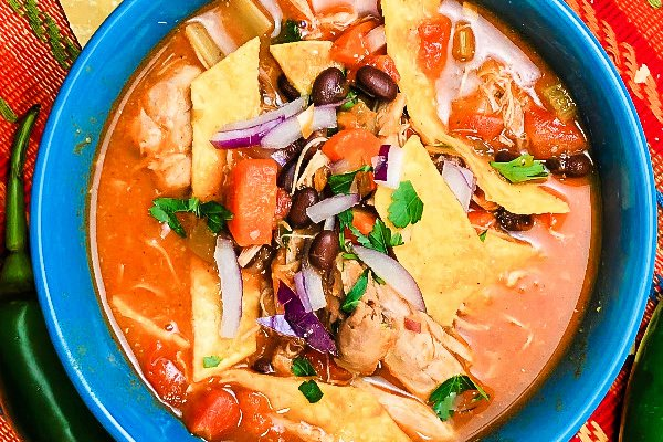 Overhead shot of a blue bowl brimming with Chicken Tortilla Soup.