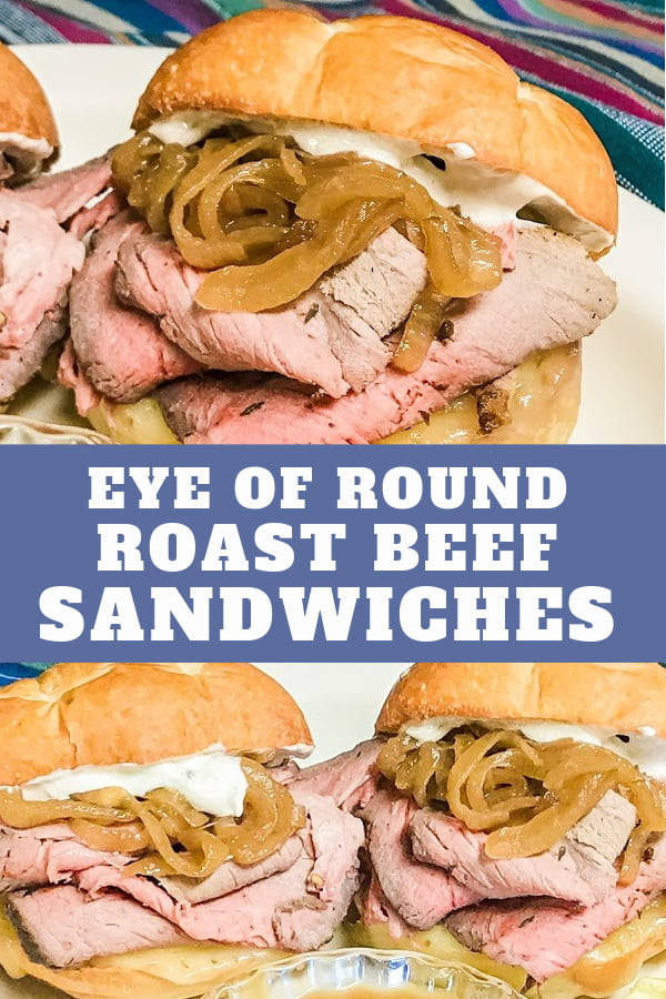 French dip sandwiches on a plate, piled with roast beef, caramelized onions and sauce.