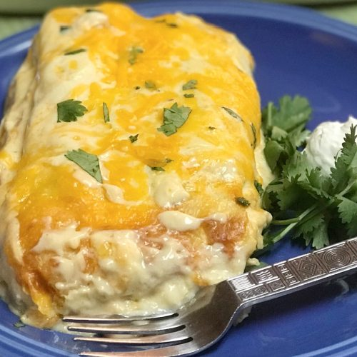 Two ground beef burritos smothered with sour cream and cheese.