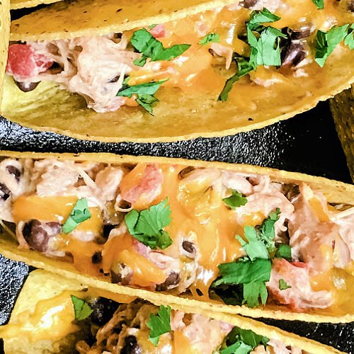 A skillet full of baked chicken tacos standing up in the pan.