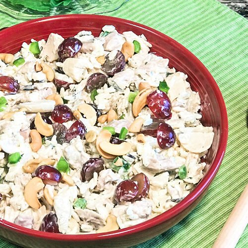 Red serving bowl loaded with chicken salad.