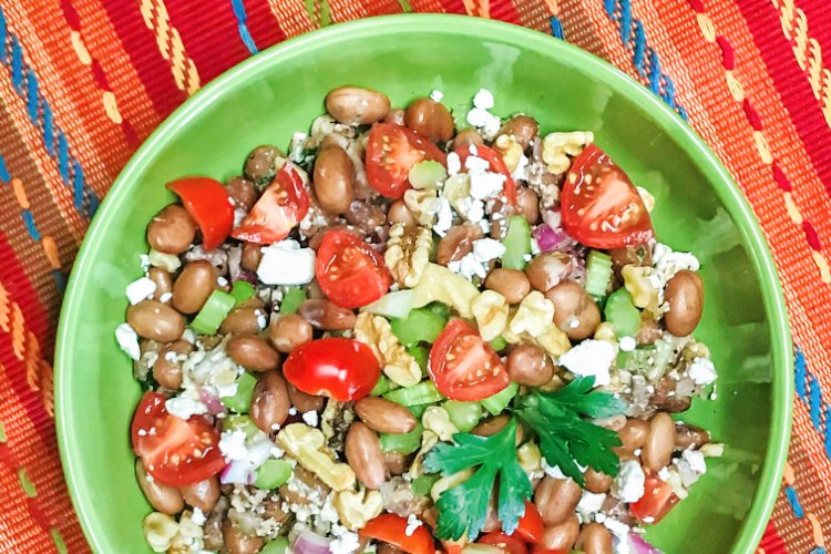 A bright green serving bowl with pinto bean salad and veggies.