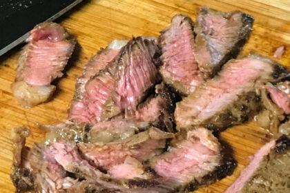 Slices of medium-rare steak on a cutting board.