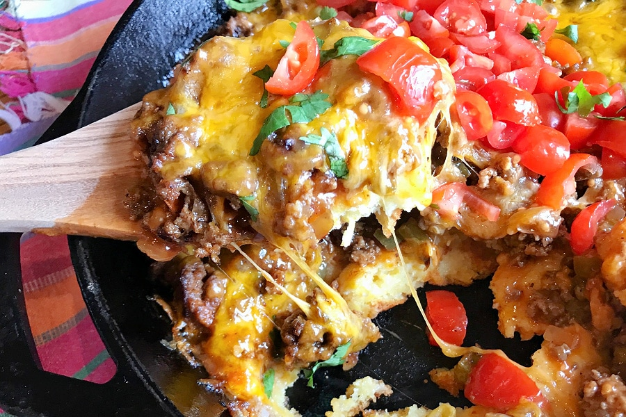 A cast iron skillet full of Tex Mex Cornbread Casserole with a big spoonful of a serving.