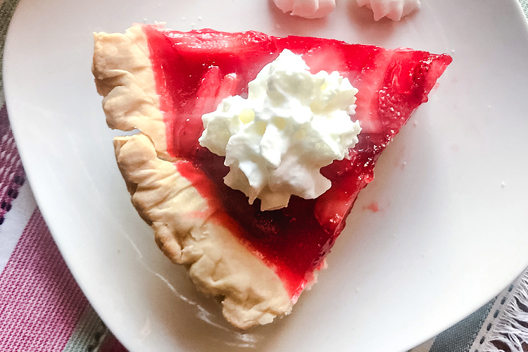 Overhead view of a slice of fresh strawberry pie topped with whipped cream.