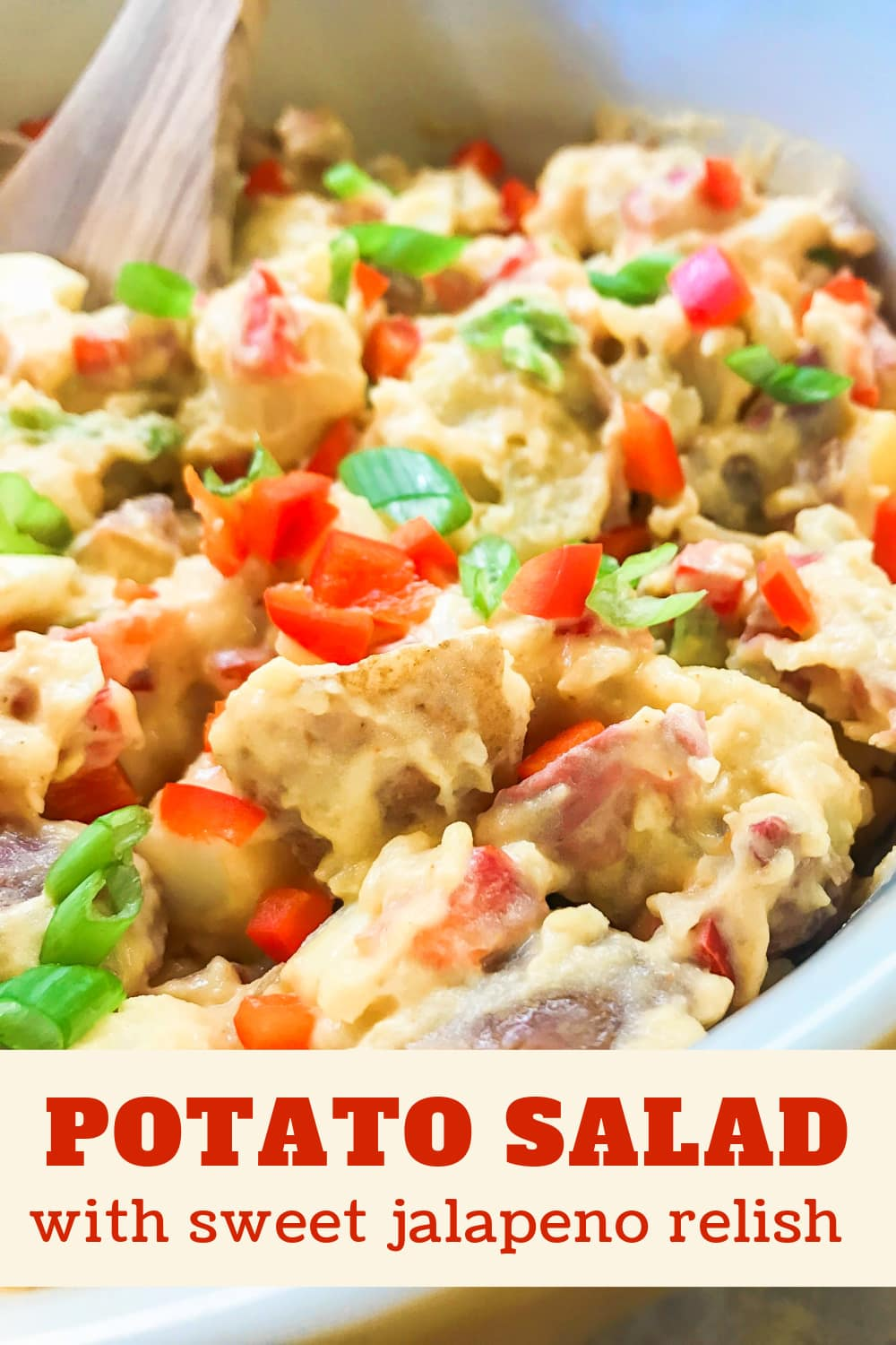 Creamy potato salad with red bell peppers and scallions on top.
