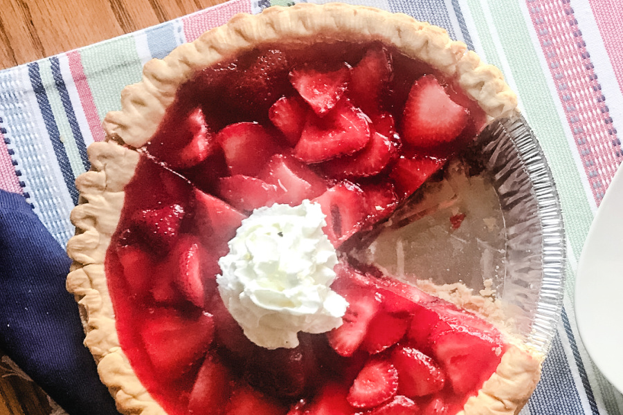Overhead shot of a strawberry pie missing a single piece.